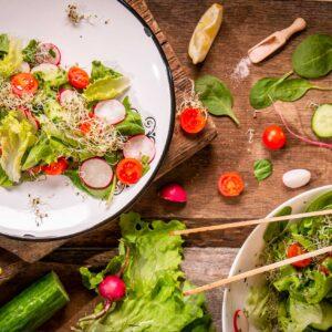 Салата с бейби спанак, репички, краставица и дресинг от мента, заснета отгоре и декорирана артистично със челенчуци