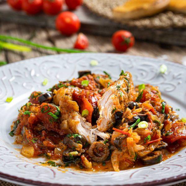 Пиле с домати и маслини заснето в близък кадър, украсено с магданоз