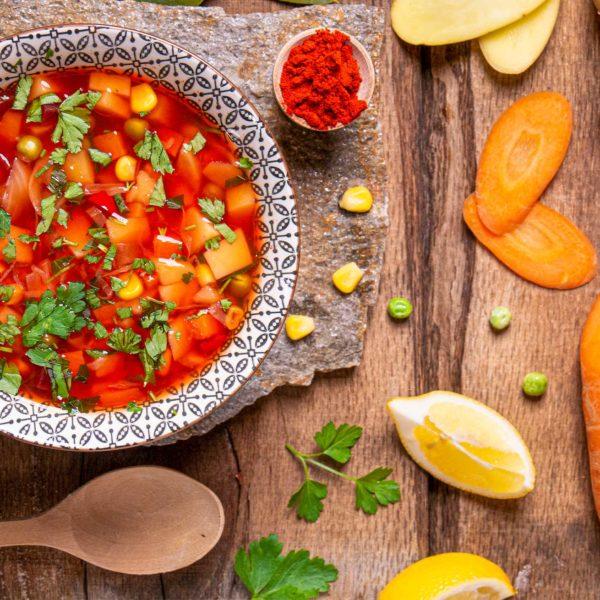 веган супа борш поръсена с магданоз и украса лимон моркови и червен пипер