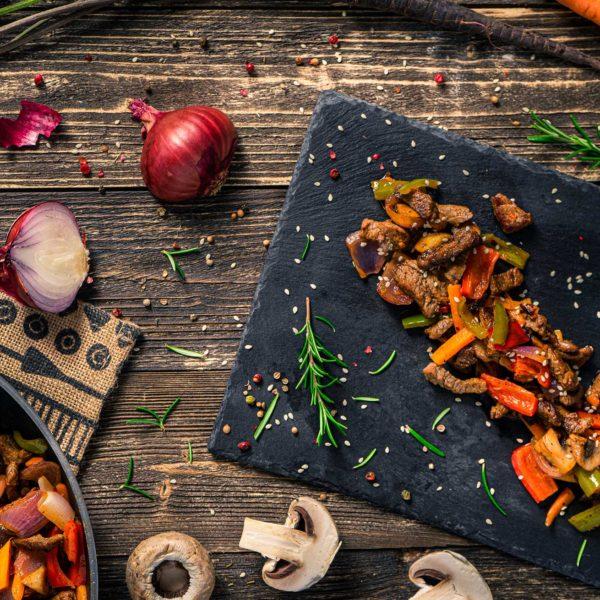 Телешко със зеленчуци, заснето отгоре, декорирано с гъби и червен лук