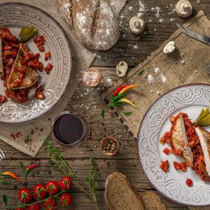 Свинска пържола по ловджийски заснета отгоре, декорирана с подправки и зеленчуци