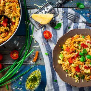 Макарони със зеленчуци заснети отгоре, декорирани с пресен лук и чери домати