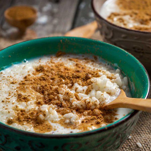 Мляко с ориз, поръсено с канела, в близък план
