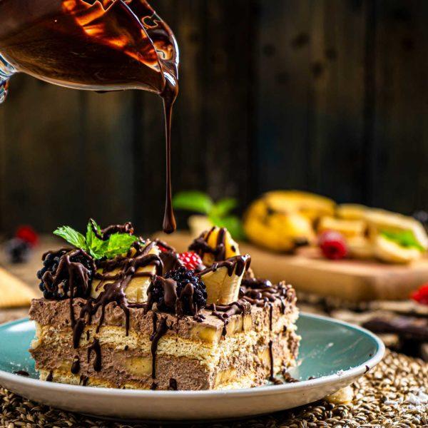 Бананова торта с обикновени бисквити заснета отблизо, залята с шоколад и декорирана с прясна мента