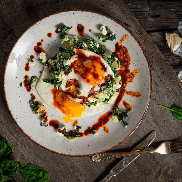 яйца върху канапе от спанак отгоре, с лук и чесън