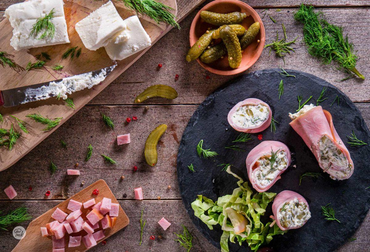 Шункови пънчета със сирене подредени върху плочка, заснети отгоре и декорирани с пресни подправки и зеленчуци