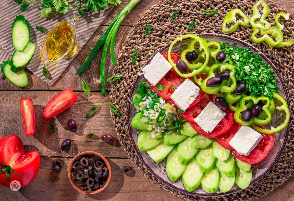 Редена салата отгоре, декорирана с лук, чушки и подправки