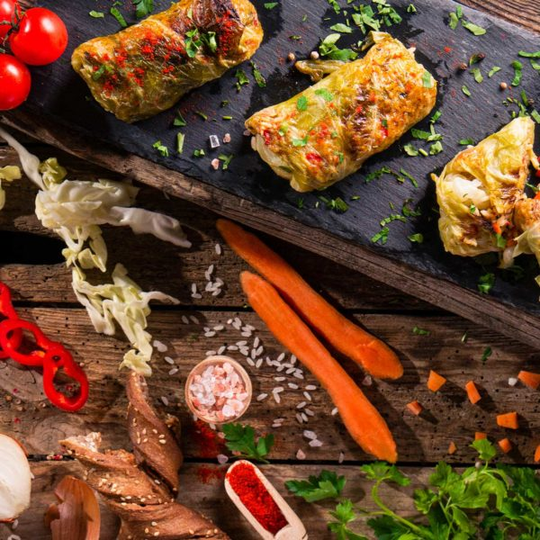 Зелеви сарми с ориз подредени върху плоча, заснети отгоре и декорирани с пресни зеленчуци и подправки