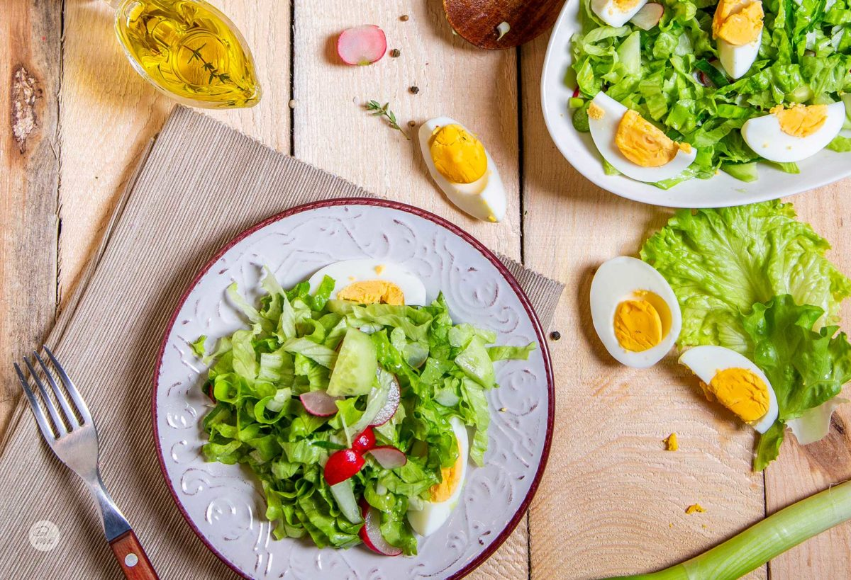 Великденска салата поднесена в чиния със сварени яйчица и пресни репички, заснета отгоре