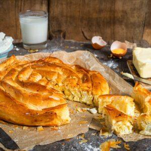 Вита баница със сирене поднесена на хартия за печене, отрязана на парче
