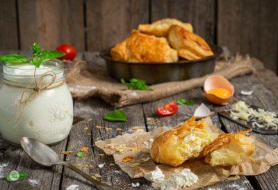 Бутер банички с кашкавал и сирене заснети отблизо, поднесени с айрянче на стара дървена маса
