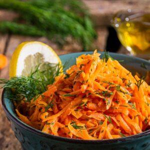 Салата от моркови заснета отблизо, поднесена в купичка с копър и лимон