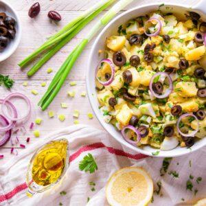 картофена салата снимана отгоре декорирана с маслини лук и зехтин