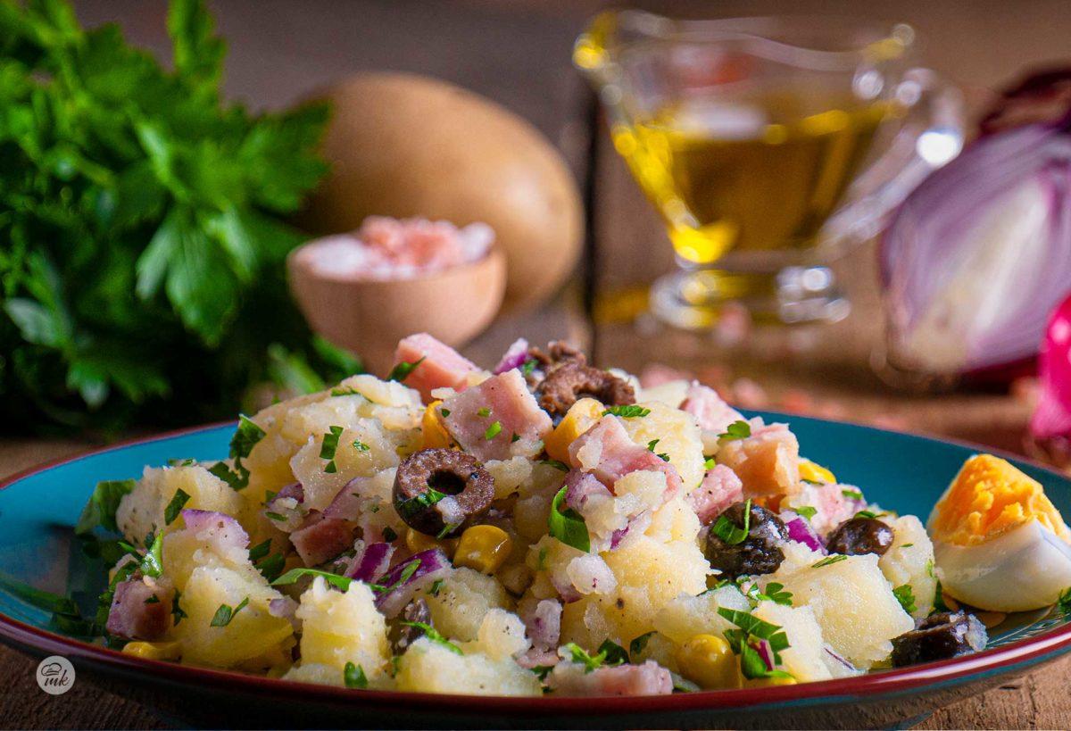 Салата с картофи, бекон и царевица Мизия заснета отстрани, поднесена в чиния, декорирана с пресни подправки