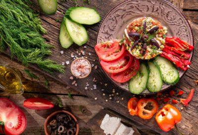 салата мозайка снимана отгоре декорирана с домати краставици сирене и маслини
