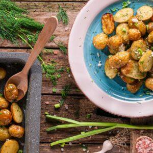 Пресни картофи с копър и чесън, заснети отгоре и декорирани с копър и пресен чесън