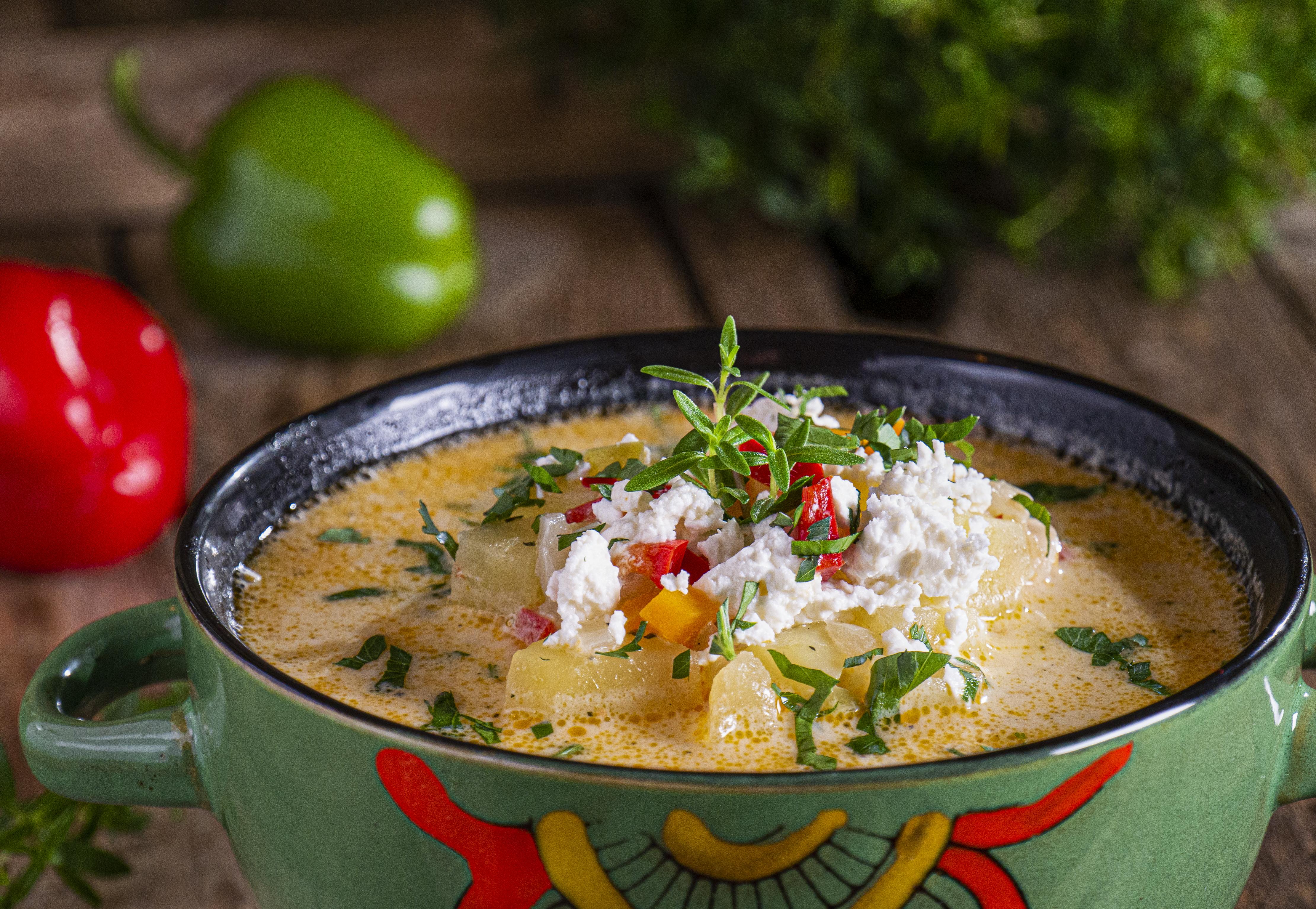 Картофена супа със сирене, заснета отблизо и декорирана с пресни подправки