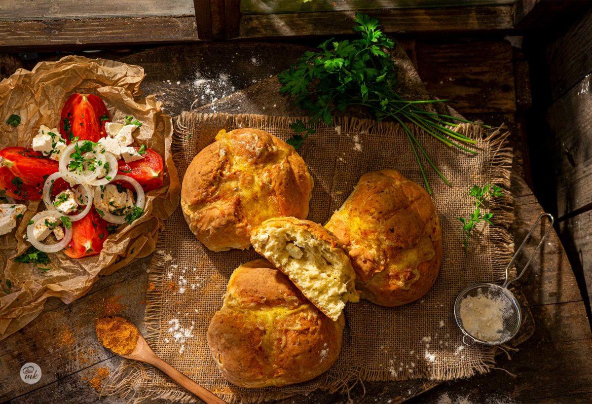 Питки със сирене и кашкавал заснети отгоре, декорирани пресни подправки, обляни от прокрадваща се светлина