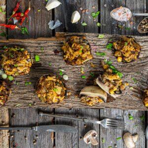Пълнени печурки с пушена скумрия заснети отгоре, поднесени артистично върху дървена дъска