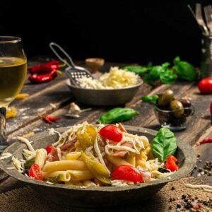 Макарони с лук и бекон заснети отстрани, поднесени в чиния с чери домати и пресен босилек