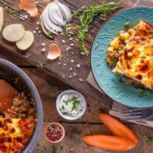 Мусака с картофи заснета отгоре, аранжирана със зеленчци и подправки