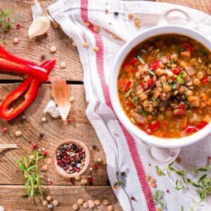 Супа от леща заснета отгоре, поднесена в купичка и аранжирана с подправки, чушки и чесън