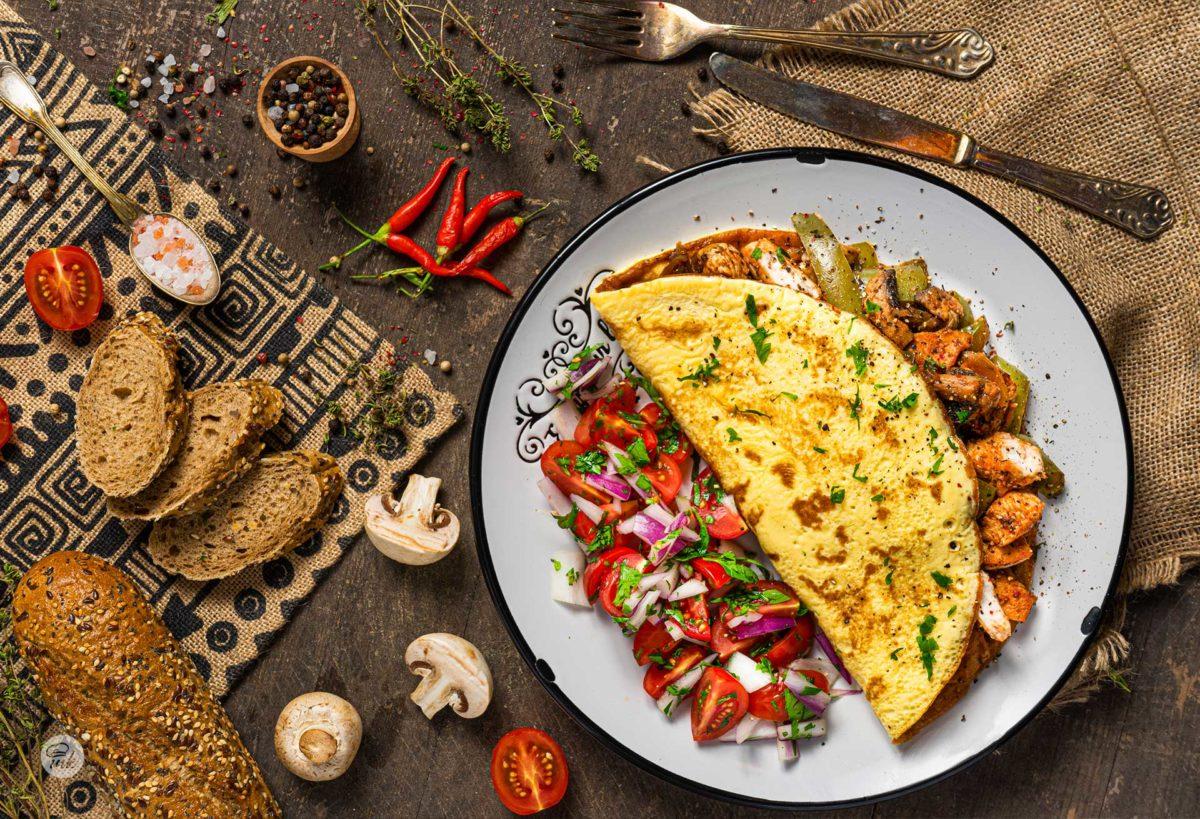 Пилешка кавърма поднесена в омлет, посипана с пресни подправки и декорирана със зеленчуци