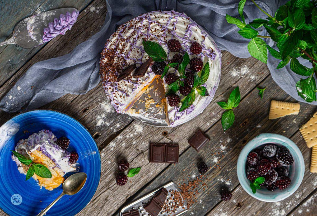 Домашна бисквитена торта със сметана отгоре, декорирана с пресни къпини и мента и оцветена със сладкарски боички