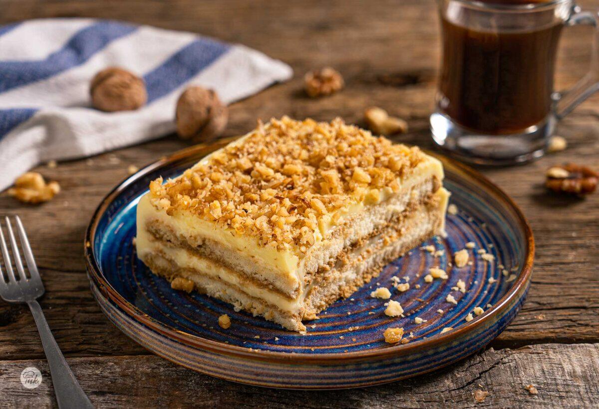 Парче бишкотена торта, поръсено с натрошени орехи, снимано отстрани