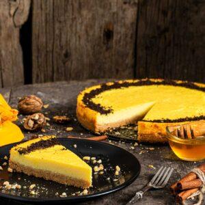 Чийзкейк с тиква, заснет отстрани, поднесен на парче в чиния и аранжиран с мед и орехи