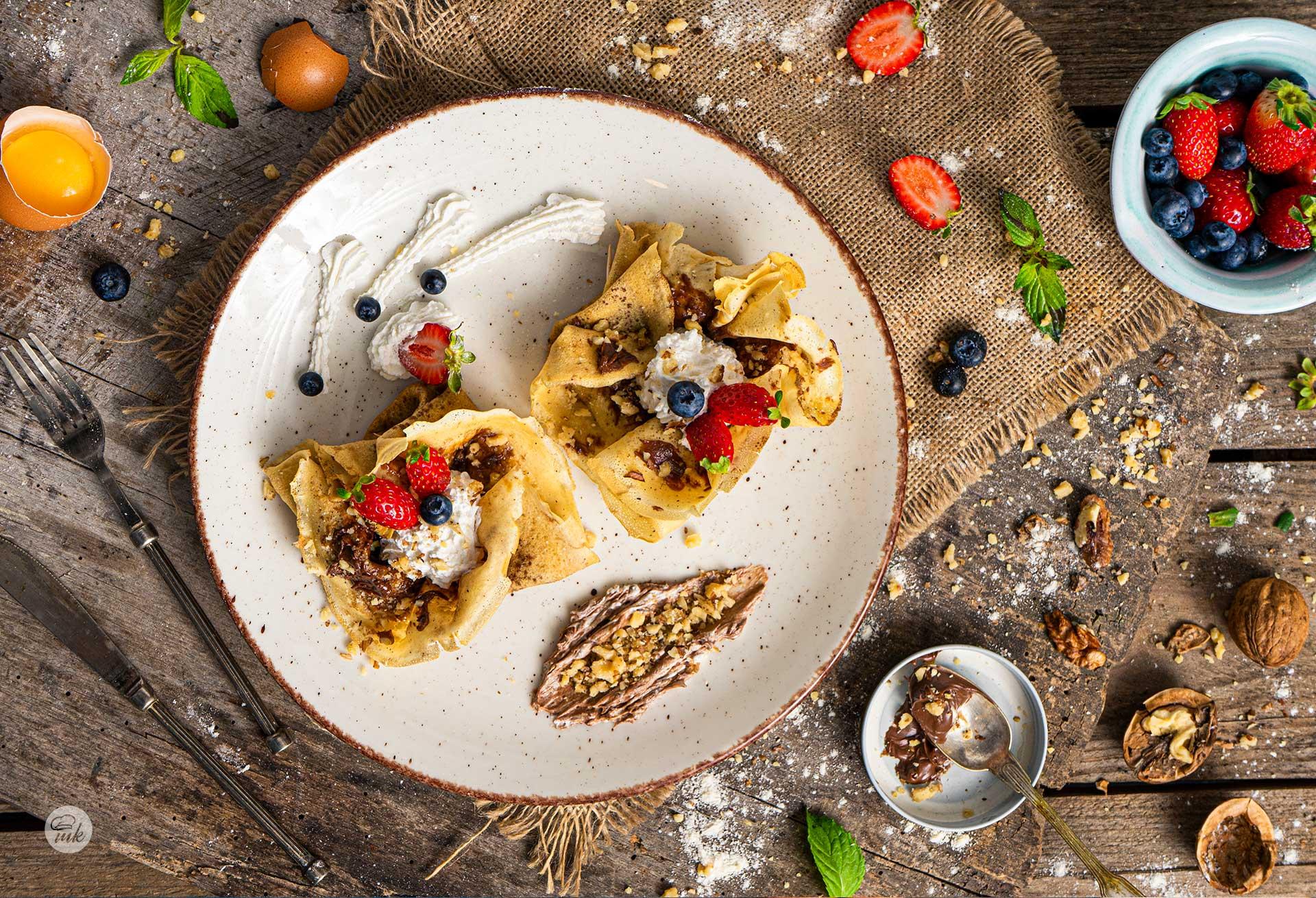 Палачинки с орехи и шоколад, заснети отгоре, поднесени във формата на розички и декорирани с ягоди и бита сметана