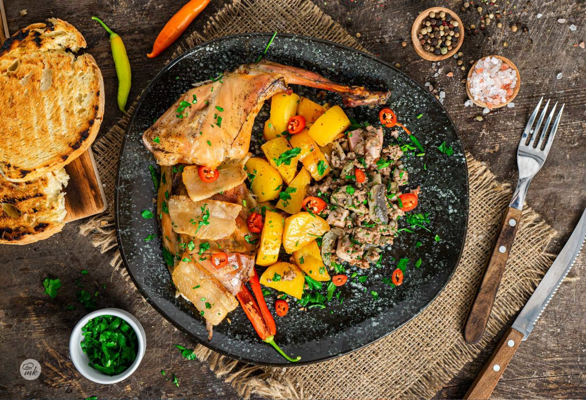 Пълнено зайче, заснето отгоре, поднесено в чиния на порция, гарнирано с плънка и картофи, поръсено с пресен магданоз