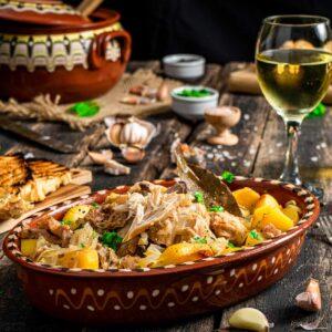 Чомлек от заек поднесен в традиционна чиния, заснет отблизо на фона на гюведжето, в което е приготвен
