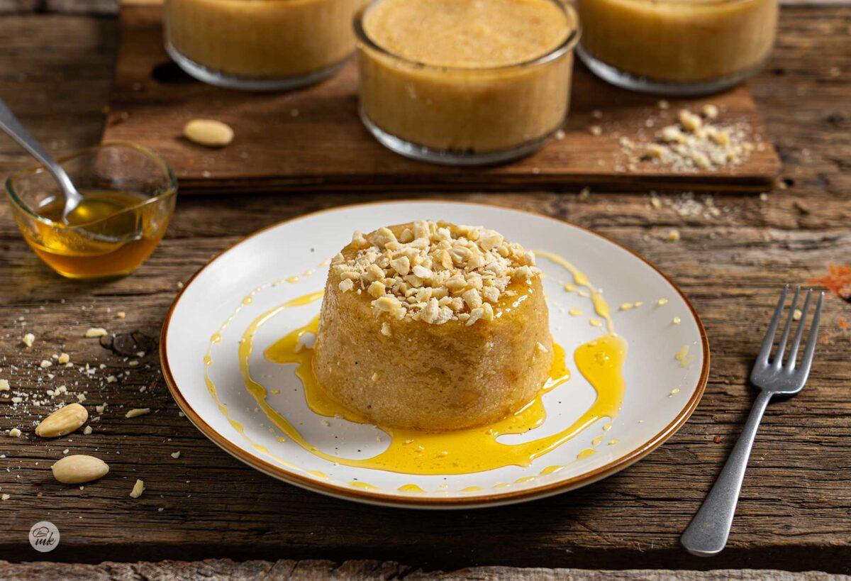 Грис халва, обърната в бяла чинийка, поръсена с начукани бадеми и мед