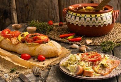 Гювеч със сирене и колбас заснет отстрани и поднесен с хлебче в порция