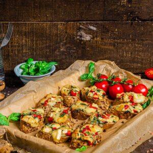Хапки със сирене бри и босилек, поднесени с чери домати, снимани отстрани