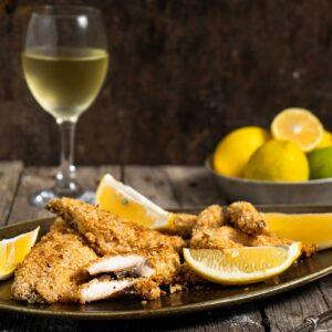 Хрупкави филенца от скумрия заснети отстрани, поднесени с чаша бяло вино и лимон