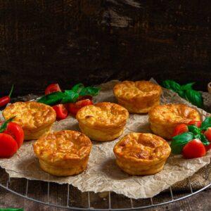Картофени кексчета със сирене, поднесени на хартия за печене с чери домати, снимани отстрани