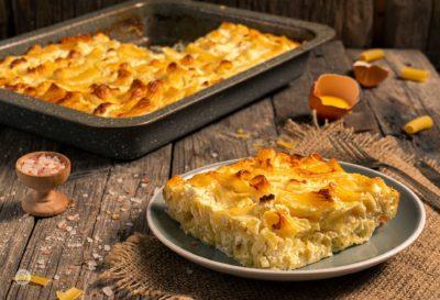 Макарони на фурна с яйца и сирене заснети отстрани, поднесени на порция
