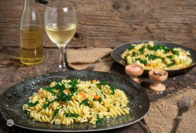 Макарони със спанак, заснети отстрани, поднесени в порция с чаша бяло вино