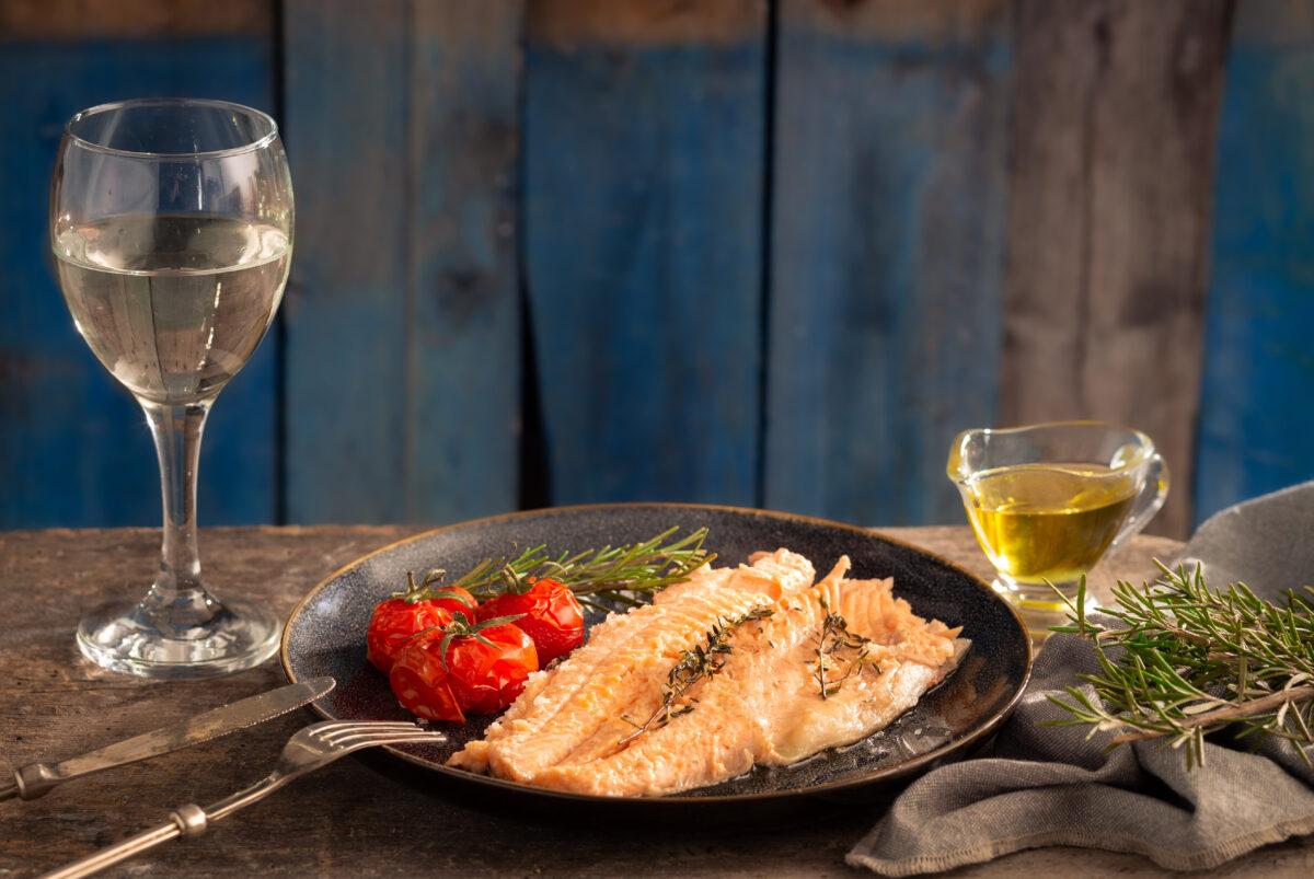 Риба в сол, поднесена с печени чери домати и чаша бяло вино