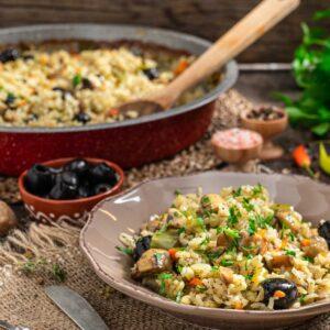 Ориз с гъби и маслини заснет в порция отстрани, поръсен с пресен магданоз