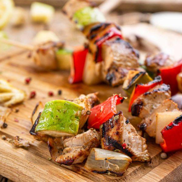 Пилешки шишчета със зеленчуци върху дървена дъска заснето в близък кадър