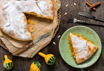 Пита с тиква, поднесена на парче в чиния и аранжирана сезонно с декоративни тикви