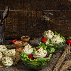 Предястие от варени яйца, поднесени със зелена салата и чери домати, снимано отстрани
