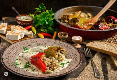 Пълнени чушки с кайма и ориз, заснети отстрани, поднесени в чиния с кисело мляко
