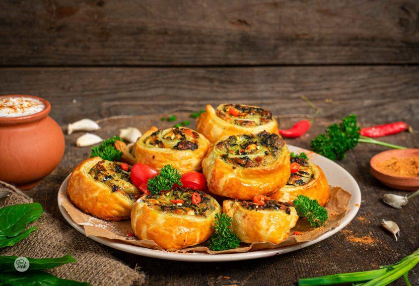 Бутерки със спанак, сирене и кашкавал, сервирани в чиния, с магданоз, чери домати и чесън, снимани отстрани