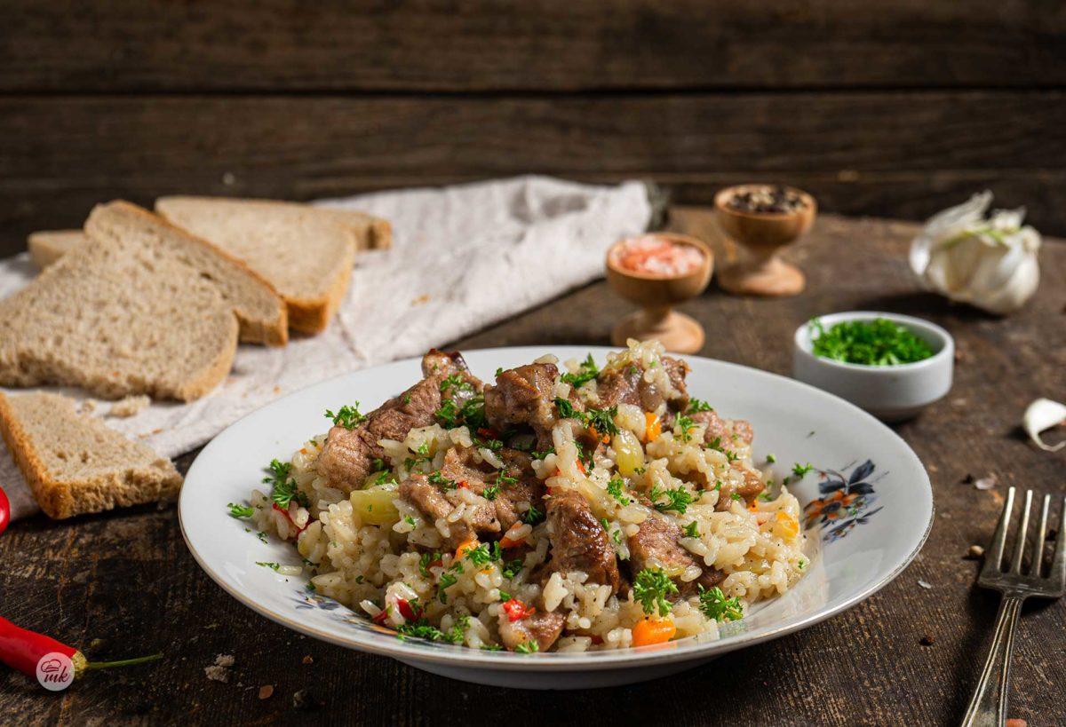 Свинско с ориз, сервирано в чиния, на заден фон с хляб, сол и черен пипер, снимано отстрани