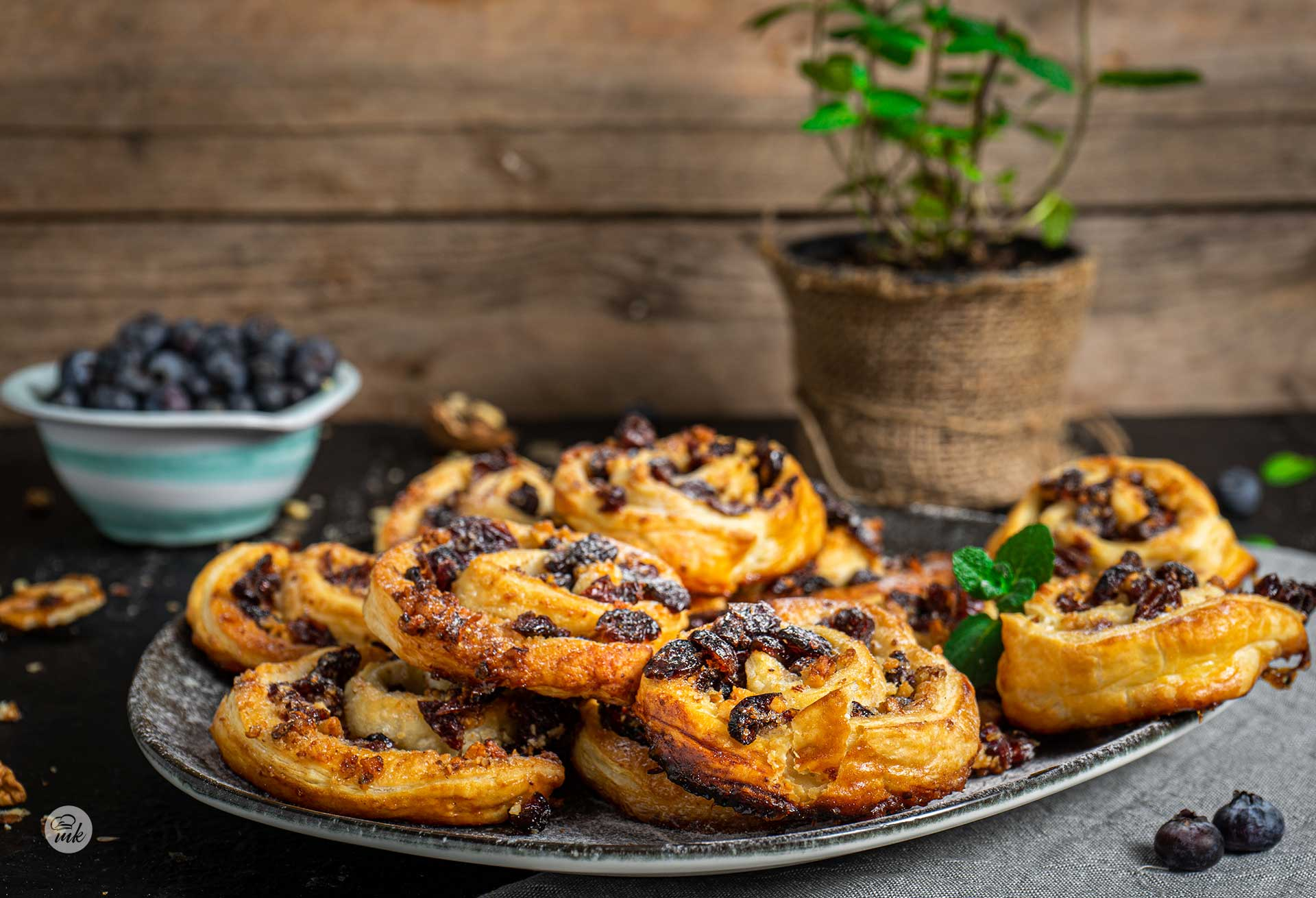 Охлювчета от бутер тесто с боровинки, сервирани в чиния, на заден фон с боровинки и мента, снимани отстрани