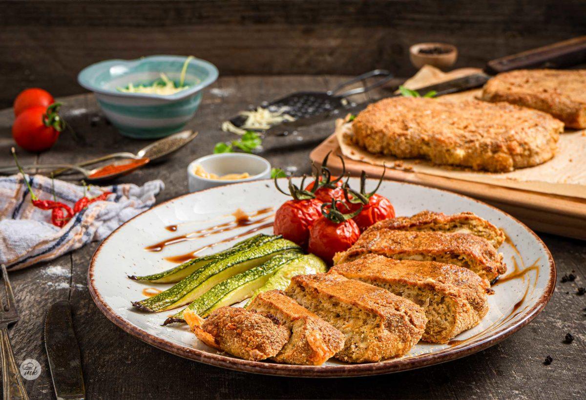 Шницел с пилешко и кашкавал, заснет отстрани и поднесен с тиквички и чери домати на фурна